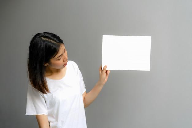 Jovem mulher que guarda um cartaz vazio para o texto em um fundo branco.