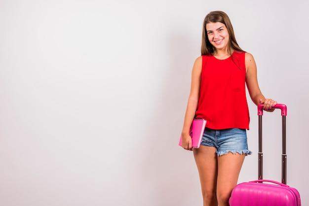Jovem mulher que levanta com mala de viagem e caderno cor-de-rosa no fundo branco