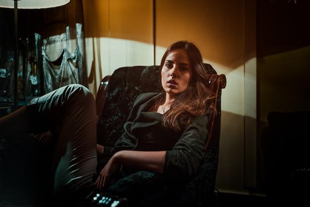 Jovem mulher que levanta em uma poltrona.