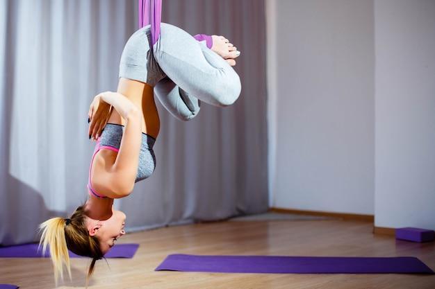 Jovem mulher que levanta fazendo o exercício aéreo da ioga com rede de cabeça para baixo.