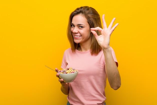 Jovem mulher que mantém uma bacia de cereais alegre e segura que mostra o gesto aprovado.