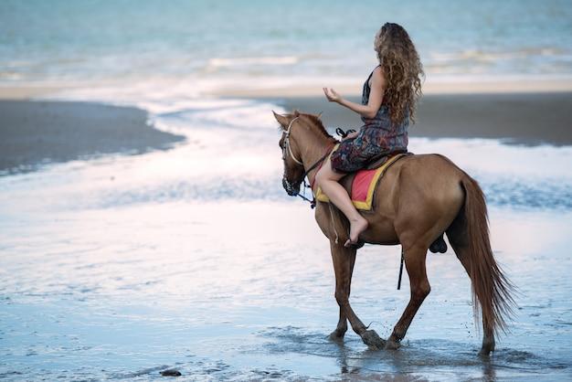 Jovem mulher que monta um cavalo na praia, conceito da viagem das férias de verão.