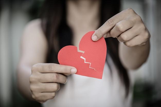 Jovem mulher que mostra o coração de papel rasgado vermelho. conceito de coração partido.