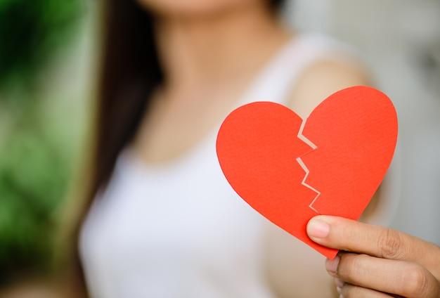 Jovem mulher que mostra o coração de papel rasgado vermelho. quebrado hearted no conceito de dia dos namorados.