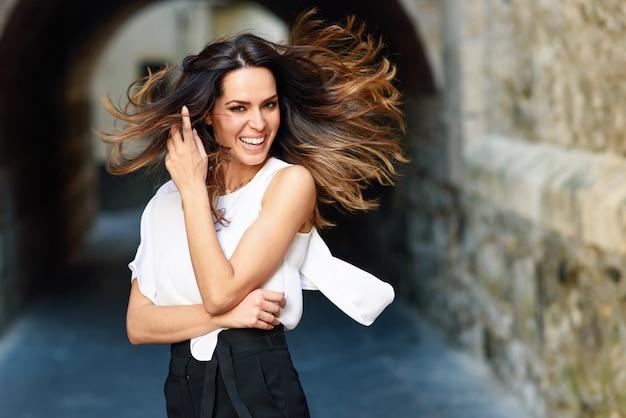 Jovem mulher que move seu cabelo longo no fundo urbano.