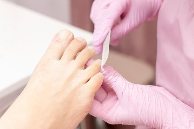 Jovem mulher que obtém o pedicure profissional em um salão de beleza, close up. as mãos de um pedicuro em luvas de borracha protetora são aplicadas com unhas nas unhas usando uma lixa de unha.