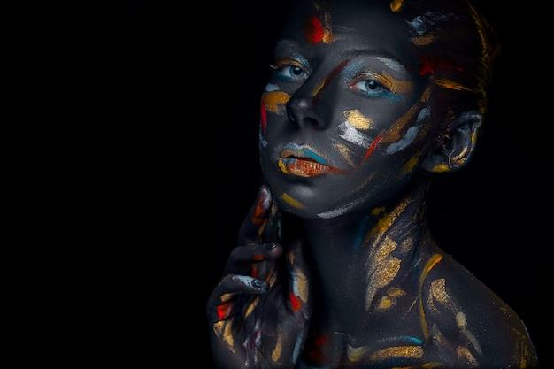 Jovem mulher que posa coberta com tinta preta