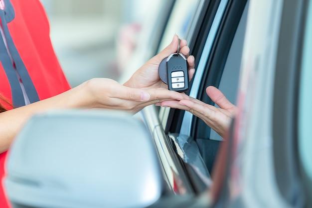 Jovem mulher que recebe as chaves de seu carro novo, foco na chave.