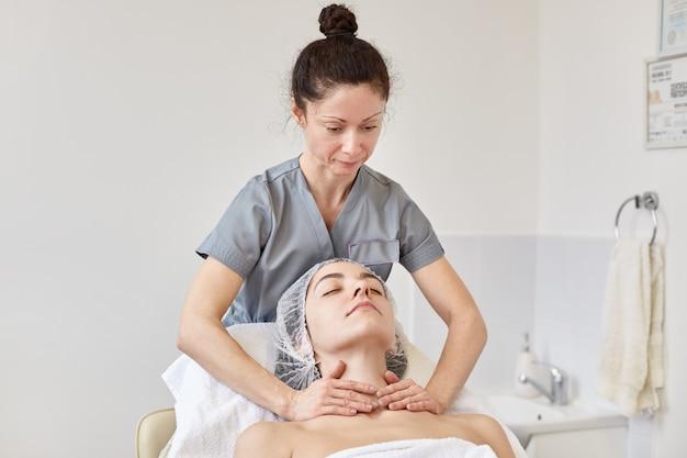 Jovem mulher que recebe o tratamento da massagem dos termas na clínica cosmetologic.