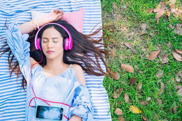 Jovem mulher que relaxa com música de escuta exterior no jardim.