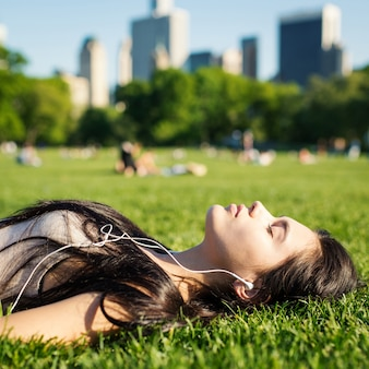 Jovem mulher que relaxa no central park que coloca na grama e que escuta a música. cidade de nova york.
