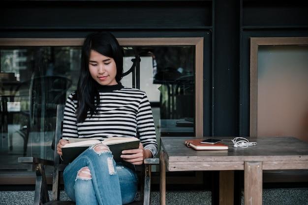 Jovem mulher que senta-se na cadeira no livro de leitura de relaxamento do café.