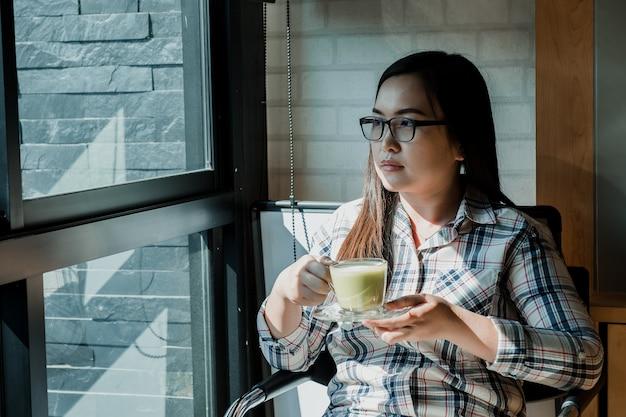 Jovem mulher que senta-se na cafetaria e no café bebendo.