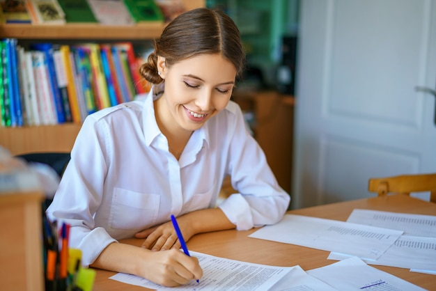 Jovem mulher que senta-se na tabela na camisa branca e nos papéis de assinatura, conceito do negócio.