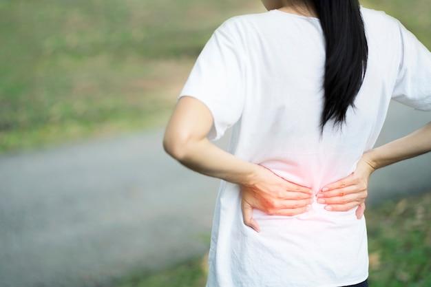 Jovem mulher que sofre da dor nas costas quando ferimento que anda para o exercício no parque, conceito da saúde.