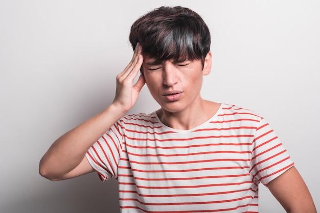 Jovem mulher que sofre de dor de cabeça isolada sobre o fundo branco