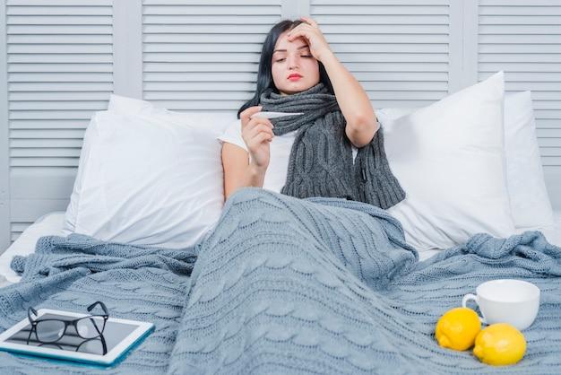 Jovem mulher que sofre de febre olhando no termômetro com tablet digital; óculos; limão e copo na cama