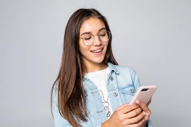 Jovem mulher que sorri e que texting em seu telefone móvel, isolado sobre a parede branca.