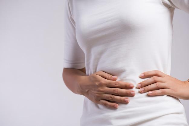 Jovem mulher que tem dor de estômago dolorosa gastrite crônica. inchaço do abdômen