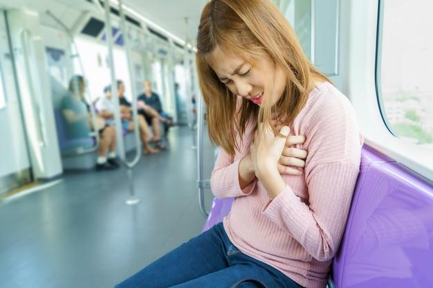 Jovem mulher que tem o cardíaco de ataque no skytrain angina pectoris, infarto do miocárdio.