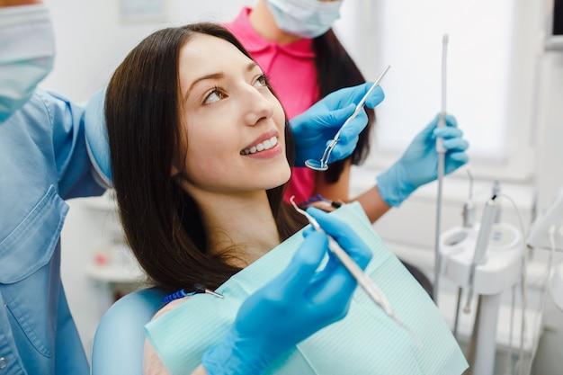 Jovem mulher que tem um tratamento dentário na clínica