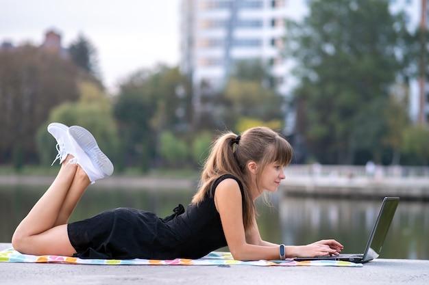 Jovem mulher que trabalha atrás do laptop deitada no parque de verão ao ar livre.