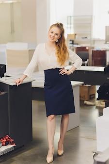 Jovem mulher que trabalha em uma fábrica de impressão. imprensa de impressão.