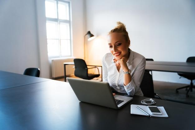 Jovem mulher que trabalha na mesa de escritório moderna com um laptop
