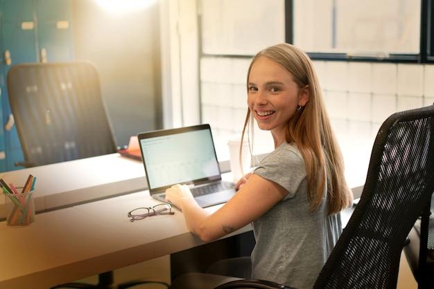 Jovem mulher que trabalha no escritório moderno de inicialização