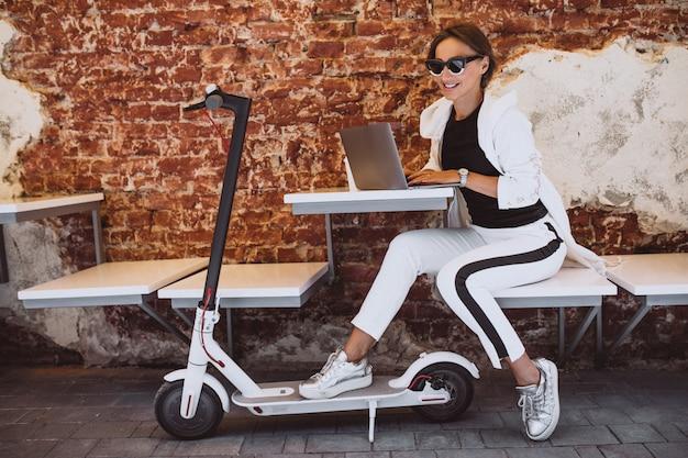 Jovem mulher que trabalha no laptop em um café