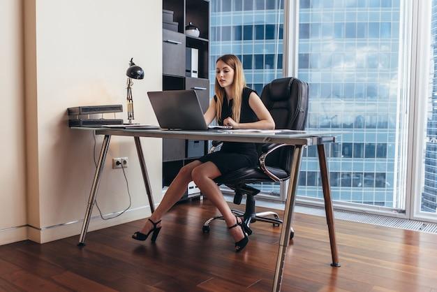 Jovem mulher que trabalha no laptop, estudando dados financeiros e estatísticas da empresa.