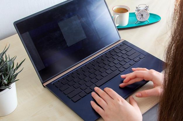 Jovem mulher que trabalha para o laptop em casa na mesa.