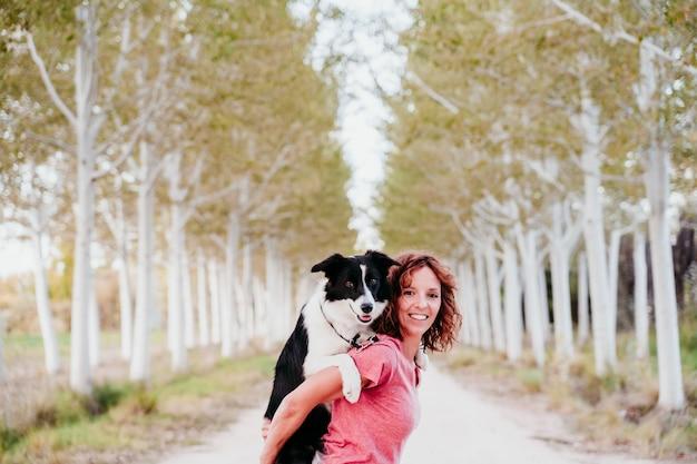 Jovem mulher que treina fora com seu cão bonito de border collie em um trajeto das árvores.