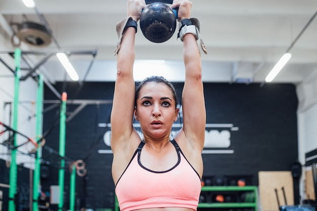 Jovem mulher que treina o kettlebell de balanço interno em um gym do crossfit
