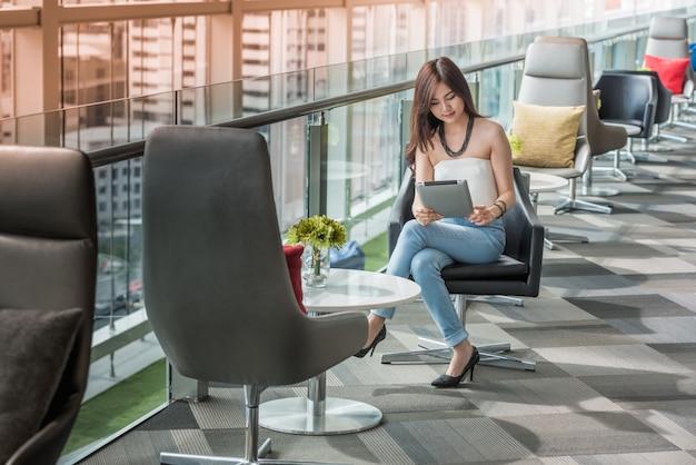 Jovem mulher que usa a tabuleta no prédio de escritórios dos vidros.