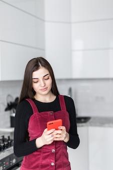Jovem mulher que usa o smartphone que inclina-se na mesa de cozinha com caneca e organizador de café em uma casa moderna. mulher sorridente, lendo a mensagem de telefone. menina feliz morena digitando uma mensagem de texto