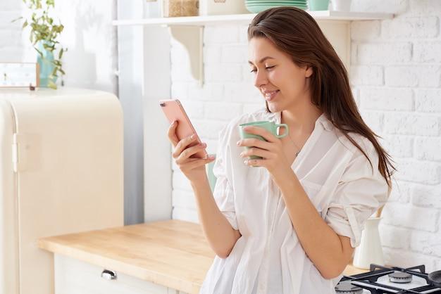 Jovem mulher que usa o smartphone que inclina-se na mesa de cozinha com caneca e organizador de café em uma casa moderna.