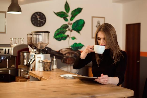 Jovem mulher que usa o tablet pc em um café.