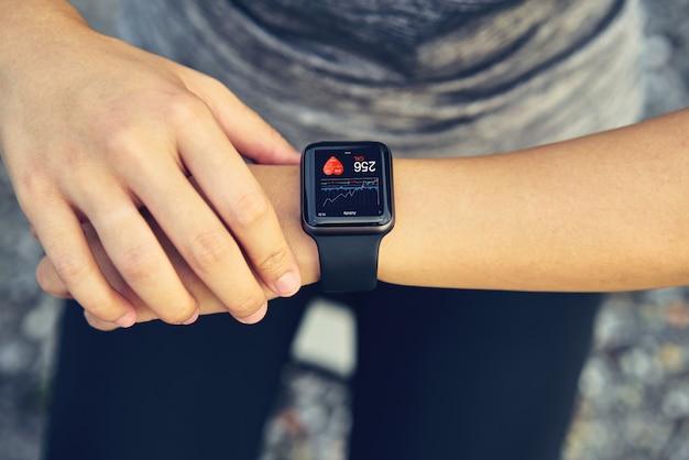 Jovem mulher que verifica o relógio de esportes que mede a frequência cardíaca e o desempenho após a corrida.