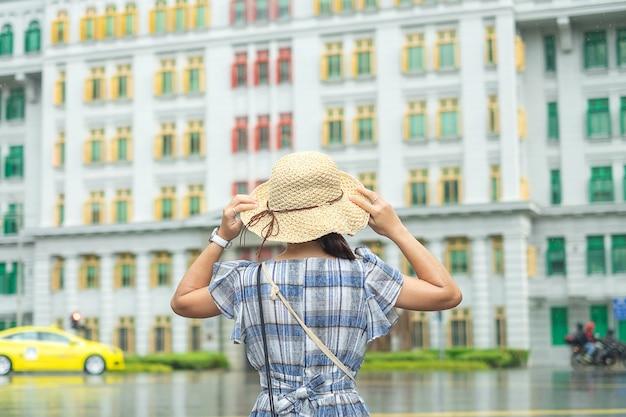 Jovem mulher que viaja com chapéu, visita asiática feliz do viajante na construção colorida do arco-íris em clarke quay, singapura. marco e popular para atracções turísticas. conceito de viagens na ásia
