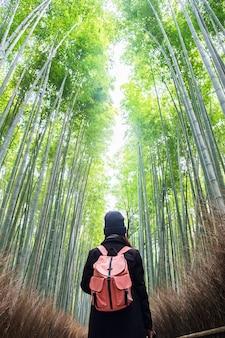 Jovem mulher que viaja no bosque de bambu de arashiyama, viajante asiático feliz que olha a floresta do bambu de sagano. marco e popular para atrações turísticas em kyoto, japão. conceito de viagens da ásia