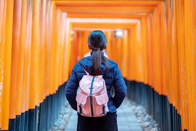 Jovem mulher que viaja no santuário de fushimi inari taisha, viajante asiático feliz que olha portões alaranjados vibrantes do torii. marco e popular para atrações turísticas em kyoto, japão. conceito de viagens da ásia