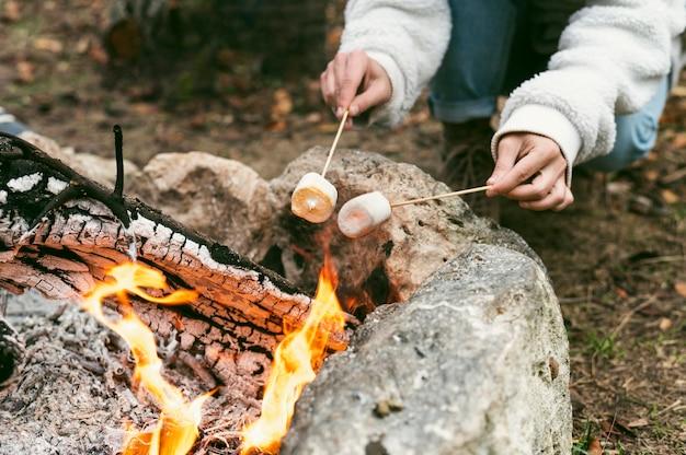 Jovem mulher queimando marshmallows em uma fogueira no inverno