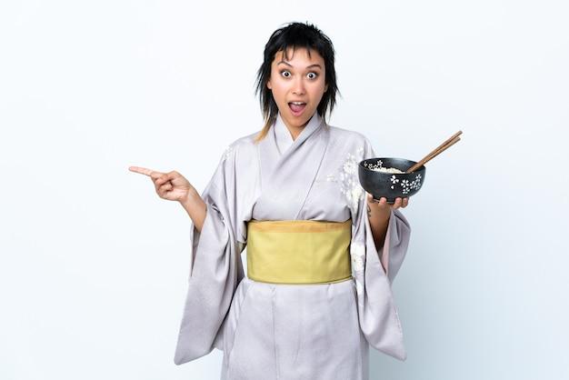 Jovem, mulher, quimono, segurando, tigela, macarrão, isolado, branca, parede, surpreendido, e, apontar lado