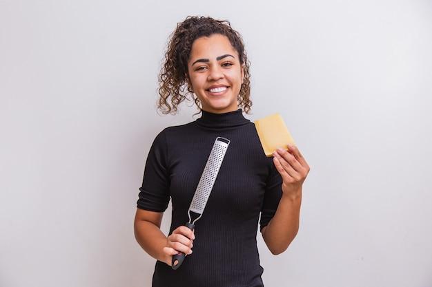 Jovem mulher ralar queijo. jovem segurando um ralador e um pedaço de queijo.
