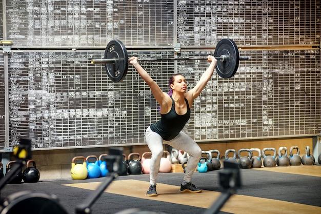 Jovem mulher realizando o arrebatar em uma academia