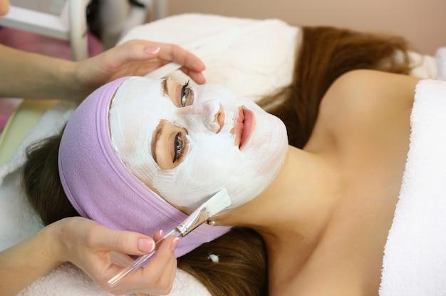 Jovem mulher recebe injeções faciais de beleza no salão.