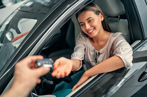Jovem mulher recebendo as chaves de seu novo carro. mulher comprando o carro.