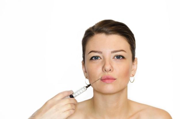 Jovem mulher recebendo injeção de enchimento, botox nos lábios para aumento.