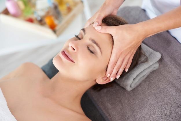 Jovem mulher recebendo massagem facial profissional